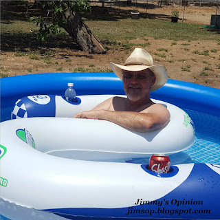 Jimmy floating in above ground pool wearing a straw cowboy hat