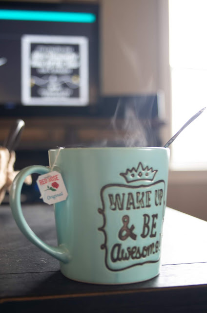 a pale blue coffee mug on a cofee table in front of a TV and a window, steam pouring from the top, a teabag sitting in it.