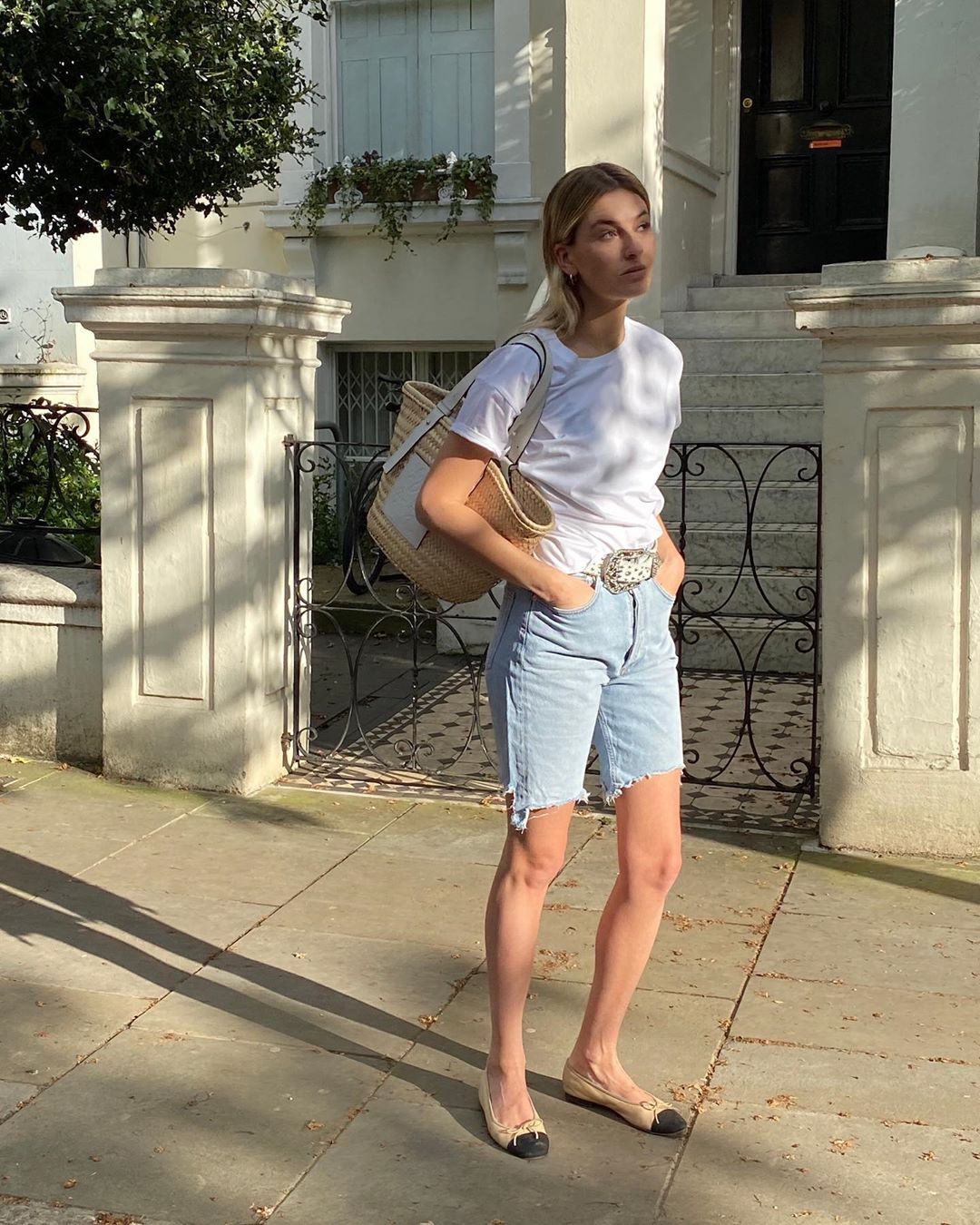 French Girl Summer Outfit Idea — Camille Charriere in a White Tee, Basket Tote Bag, Denim Bermuda Shorts, and  Chanel Cap-Toe Flats