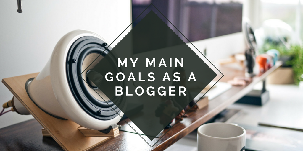 "desk background with a blank triangle on top with the blog title ""my main goals as a blogger"""