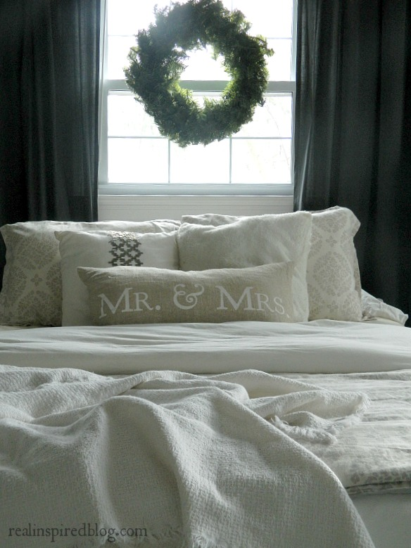 gray and white farmhouse style master bedroom with burlap pillow and wreath