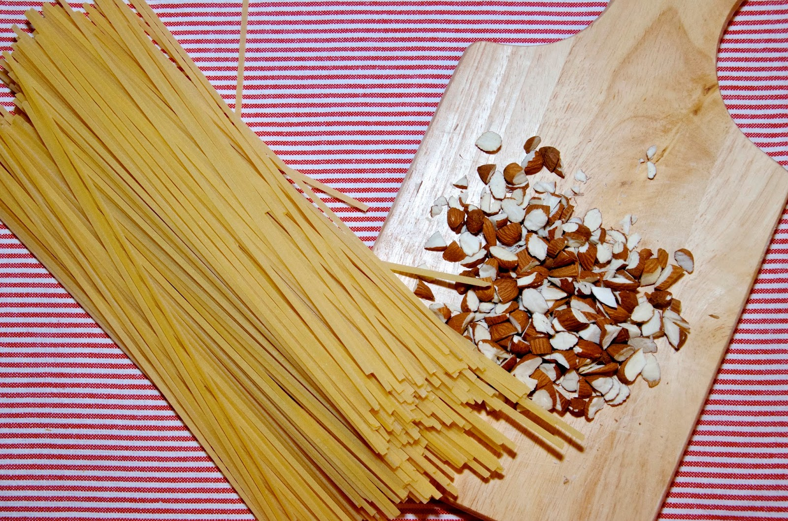 dried linguine and chopped almonds on a striped place mat with a chopping board