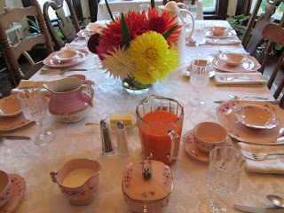 Dining room table set for breakfast (different set of china) with dahlias as centerpiece the pitcher of dark orange juice is freshly pressed carrot juice