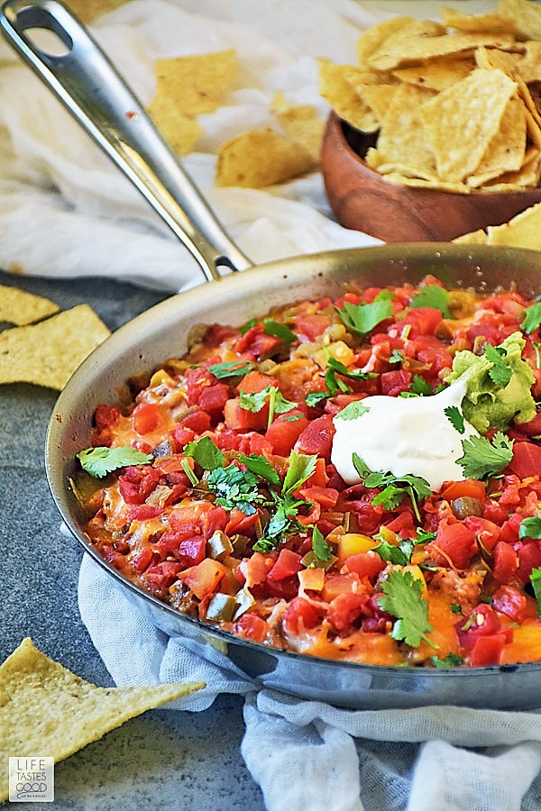 Hot Mexican Dip Skillet fresh out of the oven with melted cheese and topped with sour cream, guacamole, & fresh cilantro