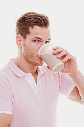 Man drinking a protein powder shake to help with weight loss.