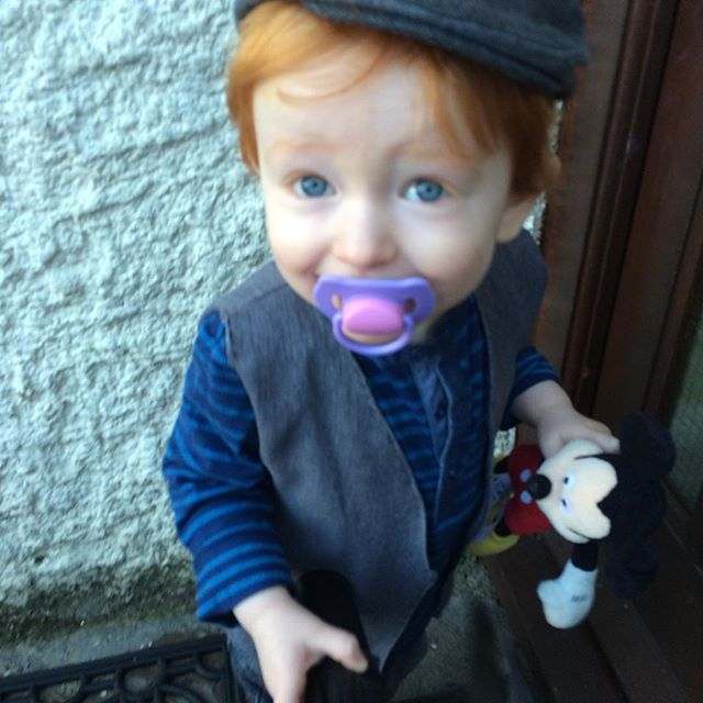 A red haired little boy in a homemade waistcoat, dressed as a chimney sweep