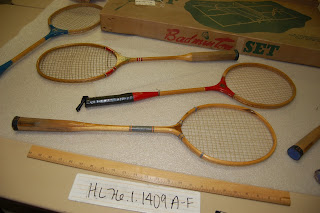 Four badminton racquets and the box they came in lie on a table with yardstick