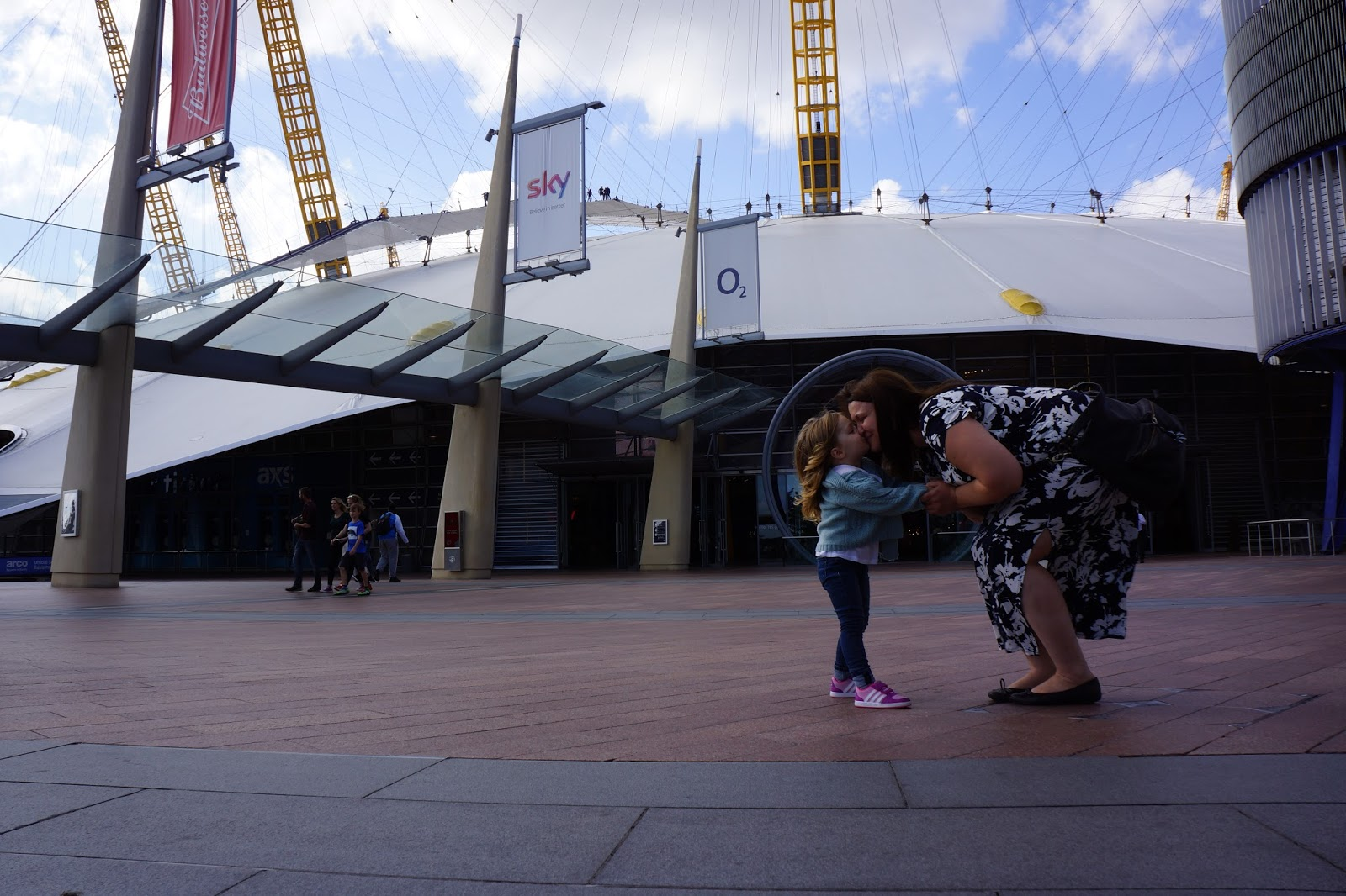 mother kissing daughter in front of the o2