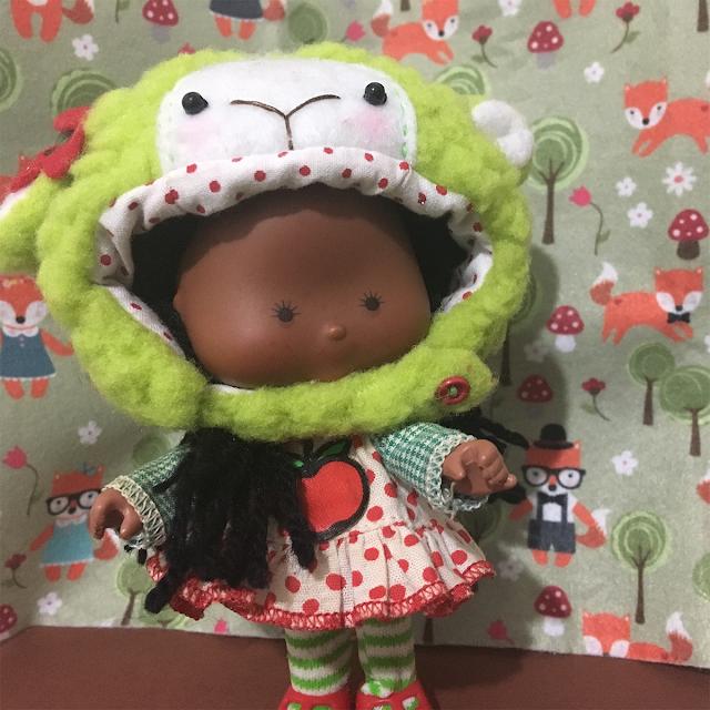 Boneca Cacauzinho usando uma fantasia de ovelhinha verde