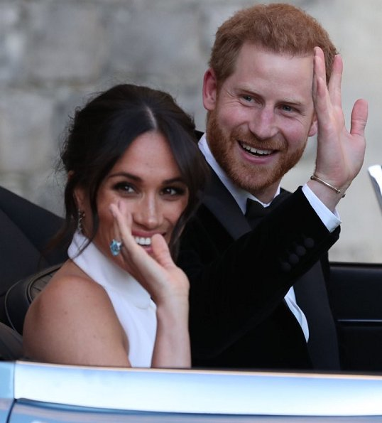 Prince Harry and Meghan Markle, Duchess of Sussex, in an E-Type Jaguar. Meghan wears a bespoke Stella McCartney high neck lily white gown