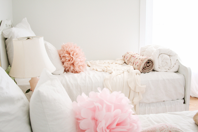 Romantic feminine farmhouse style in a girls bedroom with pink poufs on white linens #modernfarmhouse #Frenchfarmhouse #romanticbedroom