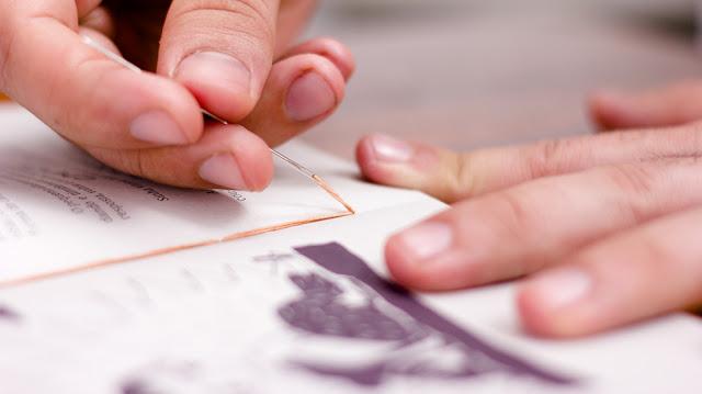 Imagem de mãos costurando os cadernos do livro.