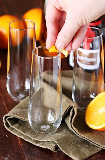 Rubbing Champagne Flute Rim with an Orange Twist Image