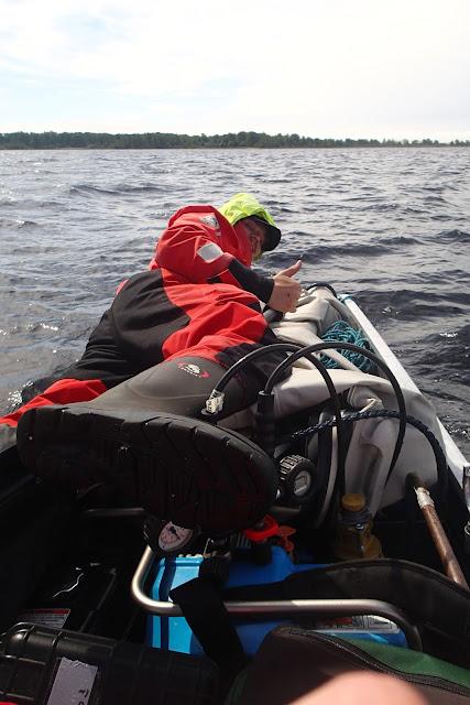 Kartoittaja makaa täpätäyden veneen päällä ja näyttää peukkua.