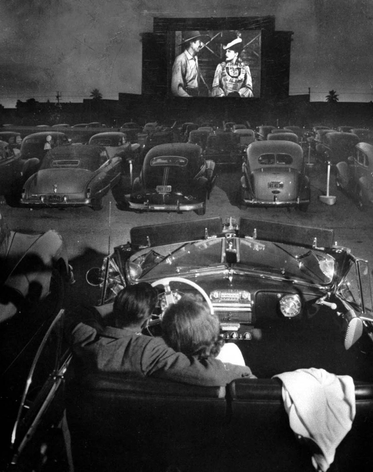 Rear view of young couple snuggling behind the wheel of his convertible as they watch large screen action behind rows of cars at a drive-in movie theater.