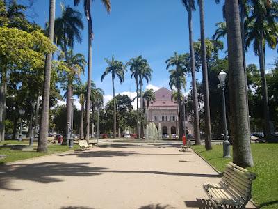 Fotografia colorida de uma das alas da Praça da República, ladeada por altas palmeiras e outras árvores. Ao fundo, a fachada rosa com detalhes brancos do Teatro de Santa Isabel e o céu azul.