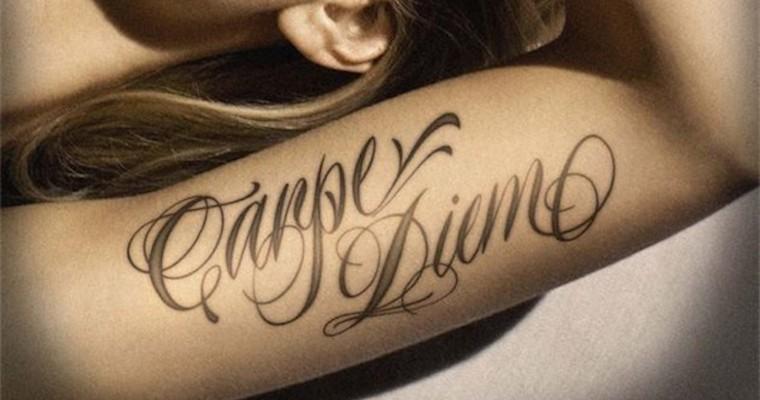 Foto del brazo de una chica en el que vemos un tatuaje con la frase Carpe Diem