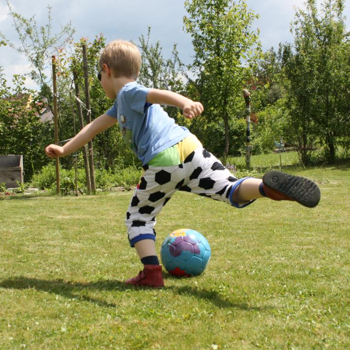 Kind tritt den Fußball in Hose aus Fußballstoff