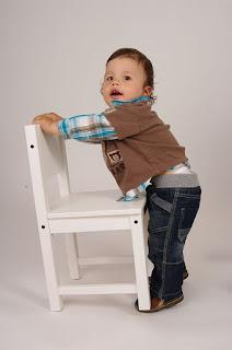 Kind hält sich an einem Stuhl fest