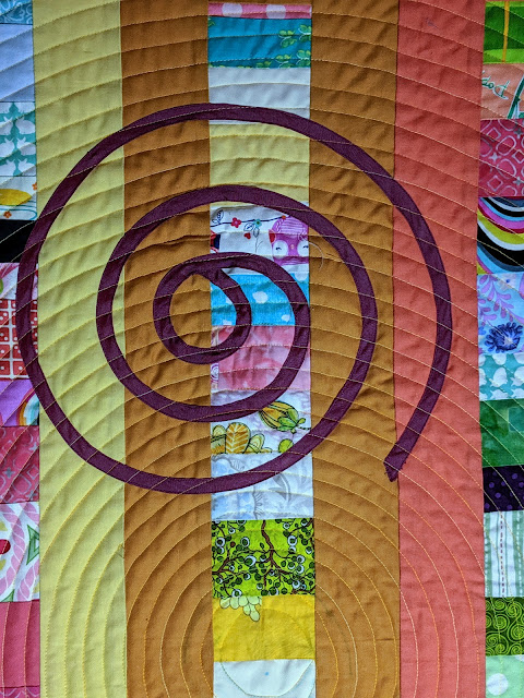 This photo highlights the spiral quilting in the center and part of one of the appliqued spirals.