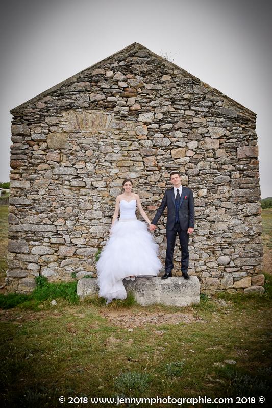 portrait des mariés photo debout main dans la main devant cabane en pierres
