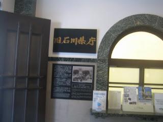 旧石川県庁の記念プレートとモダンな石造りのアーチの窓口跡