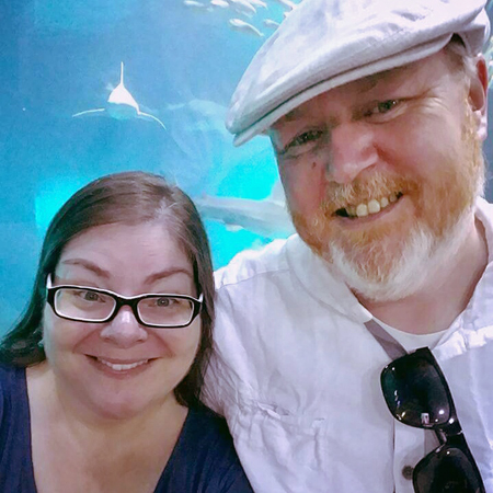 image of me and Iain at the aquarium, standing in front of a shark tank, and a shark is positioned just above my head, swimming toward us