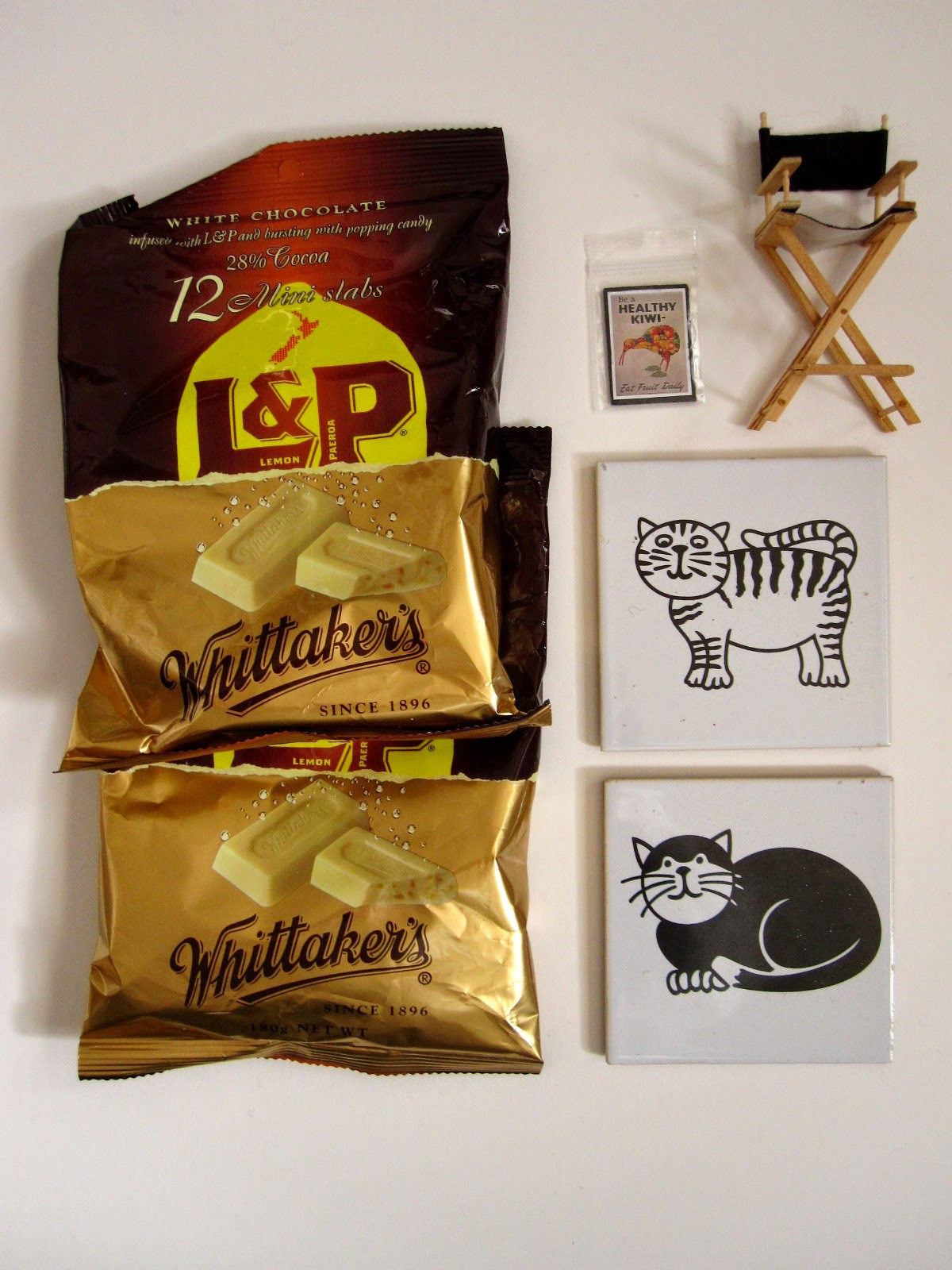 Two bags of Whittaker's L&P mini bars, two black and white cat coasters, a miniature director's chair and a miniature 'Be a healthy kiwi' poster.