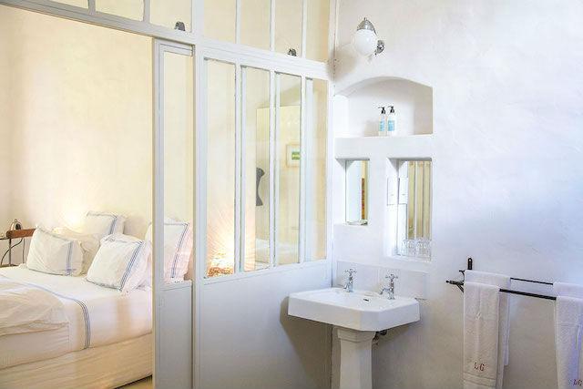 baño en suite con muro separador de madera y vidrio