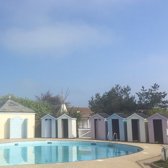 Outdoor pool and pastel coloured beach huts at Berwick, Northumberland