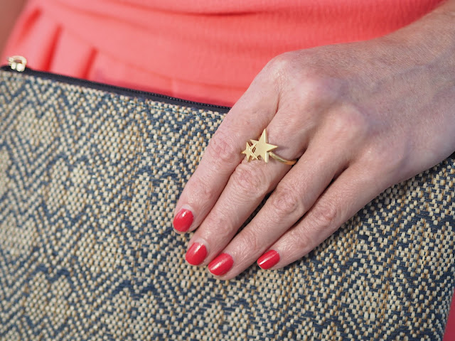 Coral asymmetric dress with gold stars jewellery and raffia clutch bag