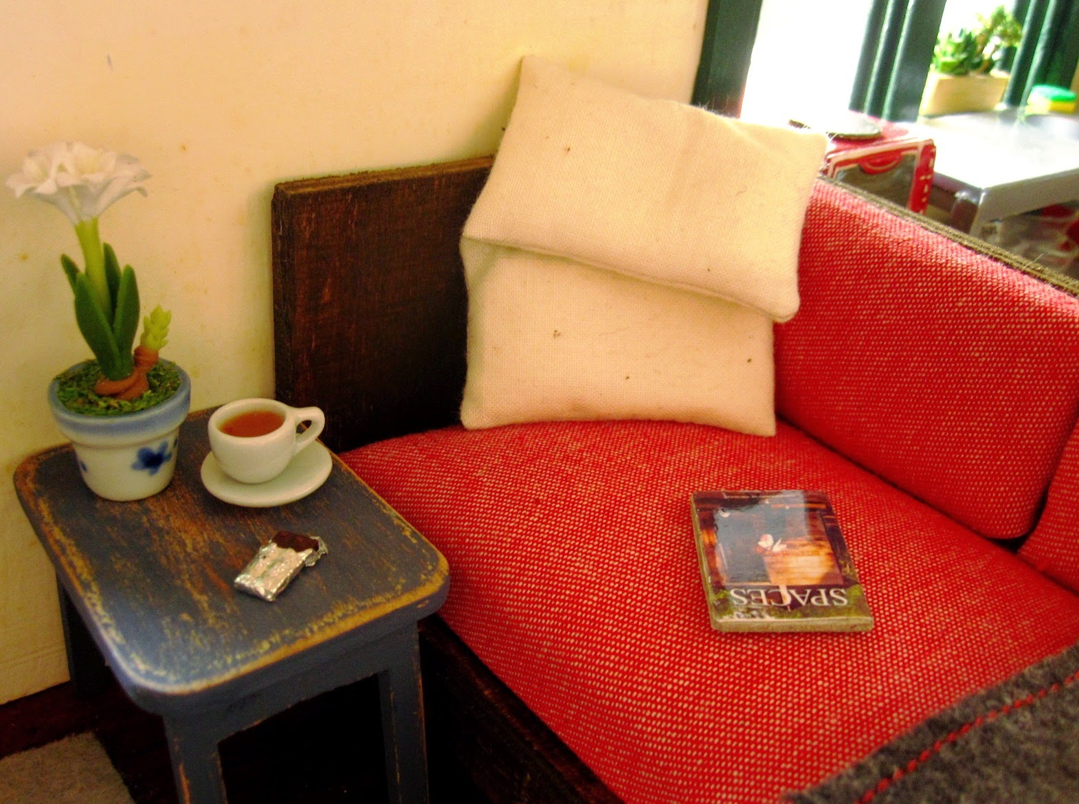 Corner of a miniature sofa, with pillows, a book and a side table holding a cup of tea and a bar of chocolate.