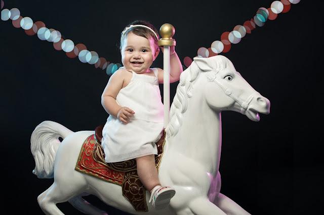 bebé feliz arriba de caballito de juguete de calesita, fotografía de estudio realizada en Roldán por Cristian Moriñigo