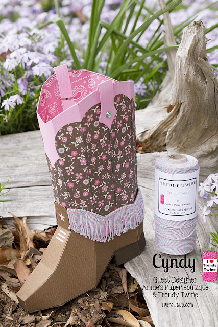 3d paper cowboy boot with a pink and blue twine fringe around the bottom half of boot