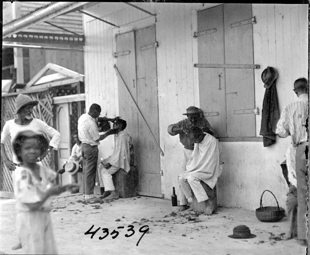 Men, possibly barbers, and men getting haircuts and shave. 1922. Guyana, South America