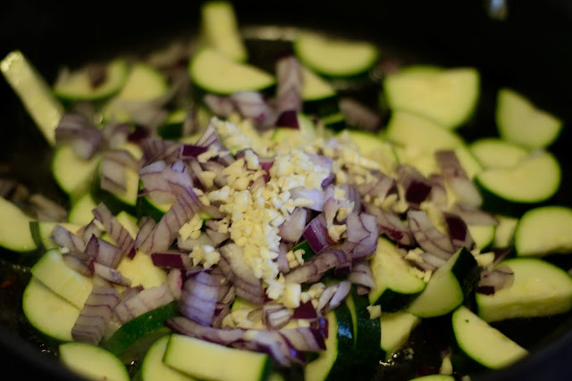 Zucchini, onion, and garlic, sautéing in a pan.