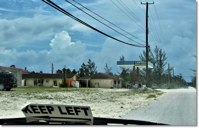 Driving down a dusty road, with powerlines and tall trees. The windshield has a 'keep left' sticker.