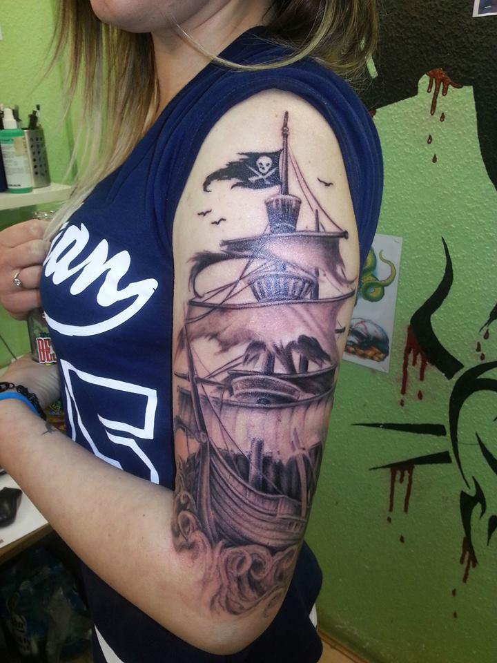 Chica con tatuaje de barco pirata en el brazo