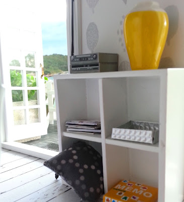 One-twelfth scale modern miniature cube bookcase next to open french doors overlooking a beach. On the shelves is a stereo system, a vase, a pile of magazines, a cushion and a game. Leaning against it is a fishing rod.
