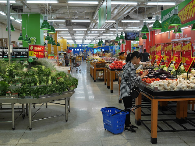 woman choosing tomatoes at a Walmart in Zhongshan, China