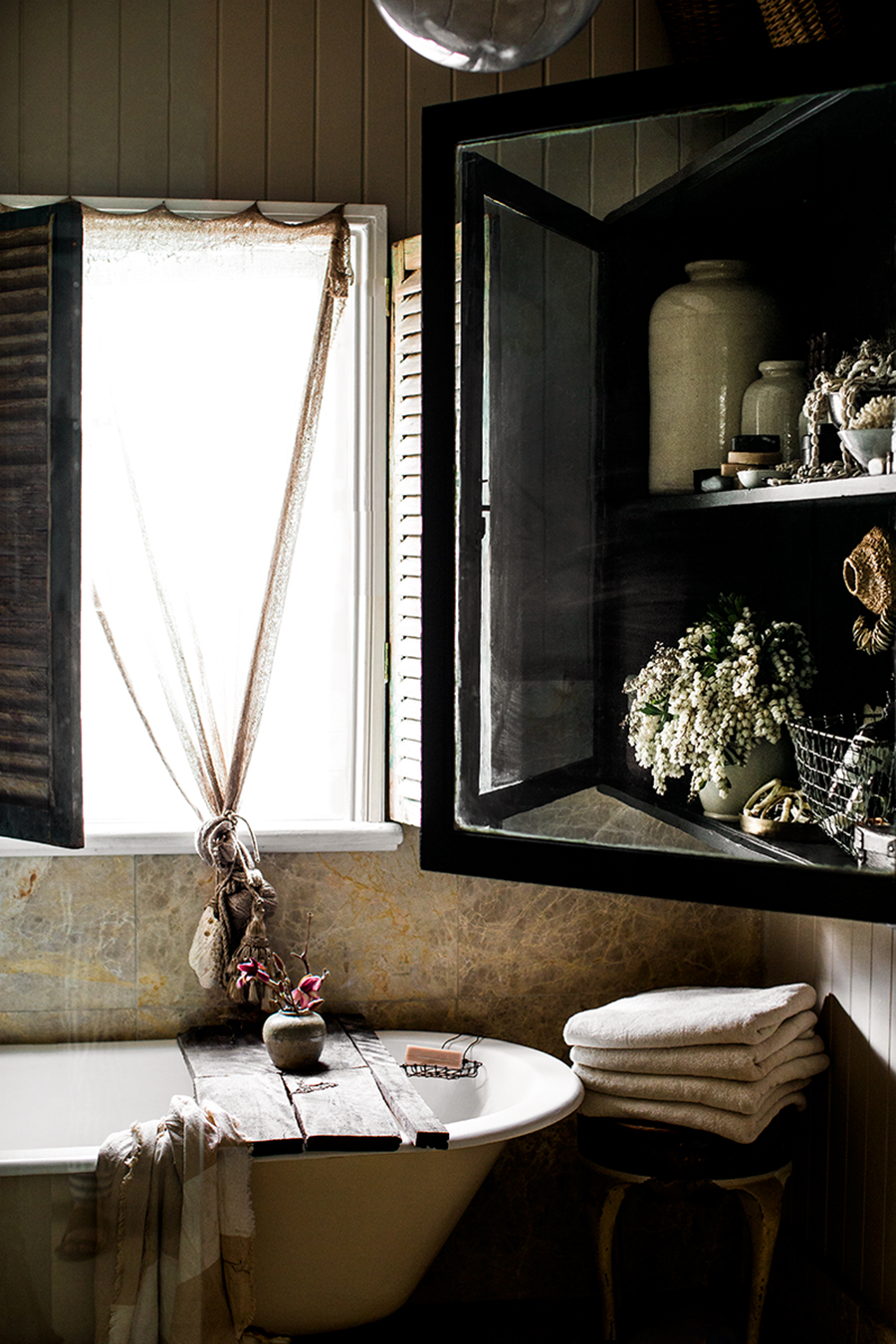Rustic Bohemian Interior Design Style in a Bathroom by Kara Rosenlund with clawfoot tub and vintage treasures. #bathroom #boho #rustic #vintage #bohemian