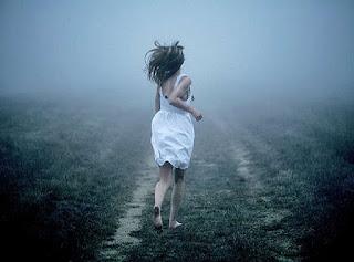 Mujer con vestido blanco y descalza huyendo por un campo hacia la niebla.