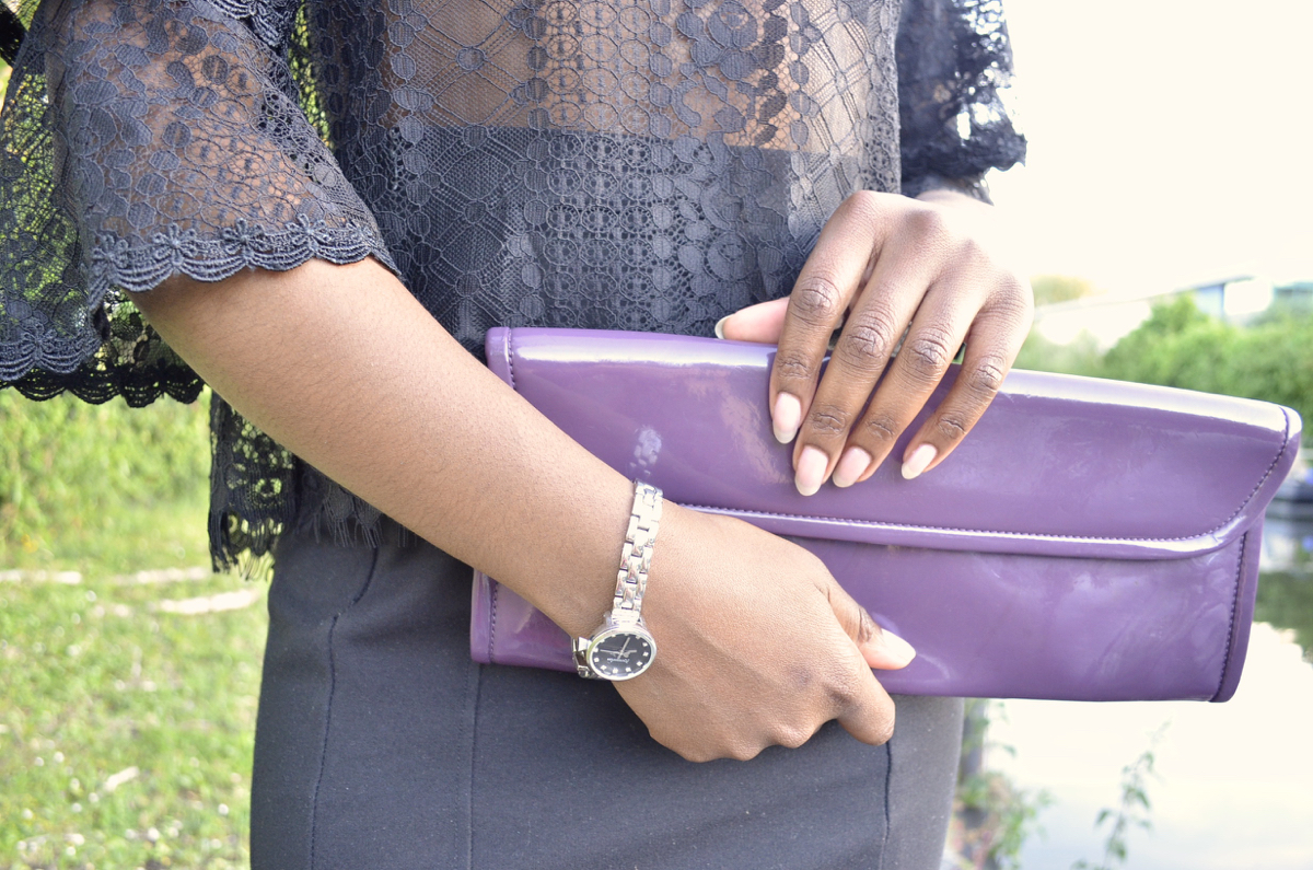 Close up shot of Aldo clutch bag and long nails