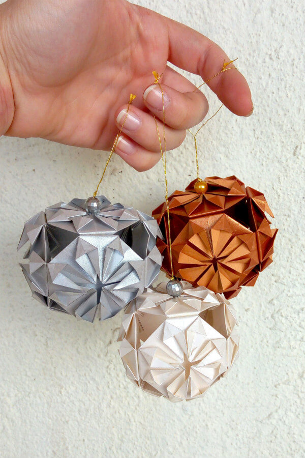 trio of metallic paper origami tree ornaments in silver, bronze, and ivory
