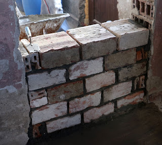 Starting to brick up the old doorway with reclaimed bricks