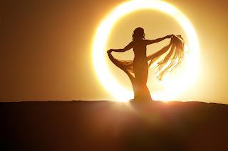 Γυναίκα με πέπλο, στέκεται μπροστά στον ήλιο. Ακολουθεί το κείμενο: Να πω πως μοιάζεις με καλοκαιριά; Μα 'σύ 'σαι πιο γλυκιά και μετρημένη. Τ' άνθια του Μάη οι ανέμοι σα θεριά δέρνουν. Το θέρος γρήγορα πεθαίνει.     Βάνει φωτιές ο ήλιος το πρωινό και άλλοτε η χρυσή του ειδή χλωμιάζει -κάποτ' η τύχη αστόλιστο, φτηνό κάνει να δείχνει αυτό που όμορφο μοιάζει.     Μα εντός σου ο ήλιος μέρα-νύχτα καίει κι ούτ' ίχνος η ομορφιά σου δεν ξεφτίζει, κι ο θάνατος δε θα 'χει να το λέει στα σκότη του πως ζεις και πως σ' ορίζει.     Όσον ο κόσμος βλέπει κι ανασαίνει θα ζει το ποίημα αυτό, να σ' ανασταίνει.