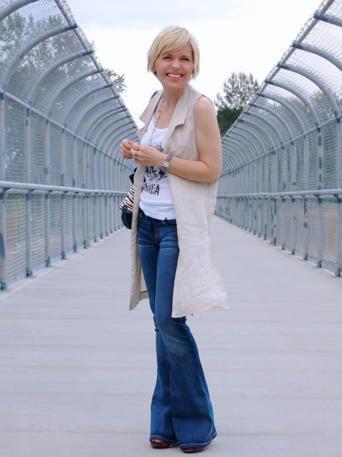 styling flare jeans with a graphic tank top and a Zara sleeveless linen coat