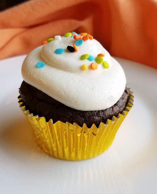 close up of chocolate pumpkin cupcake with frosting and sprinkles