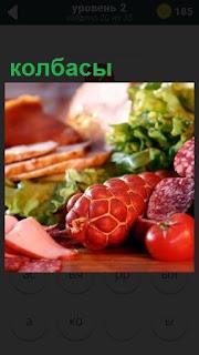 На столе лежат различные колбасы, помидоры и некоторая зелень