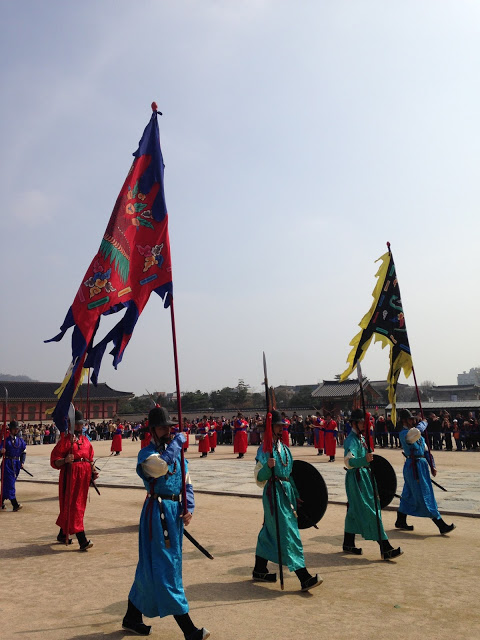 reenactors march at palace in seoul wearing brightly colored uniforms and carrying flags